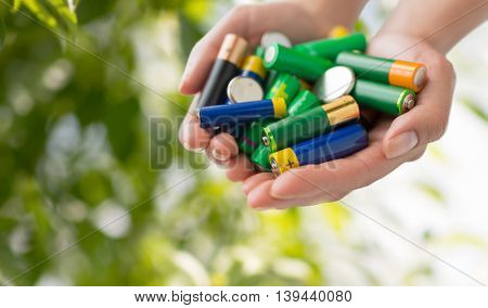 recycling, energy, power, environment and ecology concept - close up of hands holding alkaline batteries heap over green natural background