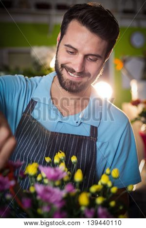 Male florist preparing flower bouquet in the flower shop
