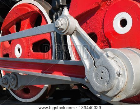 Fragment of old steam locomotive with red wheels