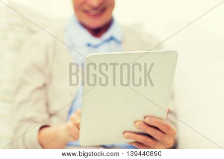 technology, age and people concept - close up of happy senior woman with tablet pc computer at home