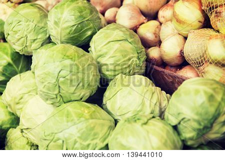 sale, harvest, food, vegetables and agriculture concept - close up of cabbage and onion at street market