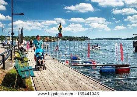 VAXHOLM, SWEDEN - JUNE 25, 2016: People walking at seaside at little cosy island Vaxholm near Stockholm