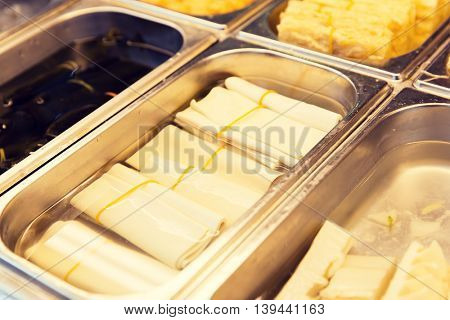cooking, asian kitchen, sale and food concept - spring rolls and snacks at street market