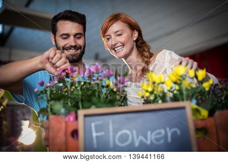 Couple preparing flower bouquet in the flower shop