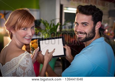 Portrait of couple using digital tablet in the flower shop