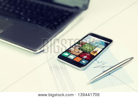 business, technology and mass media concept - close up of smartphone with news application on screen, laptop computer and pen on office table