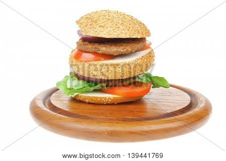 big double roasted hamburger on wooden plate with cutlery isolated  over white background