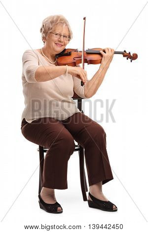 Vertical shot of a mature female violinist playing a violin seated on a chair isolated on white background