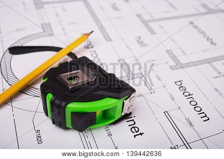 Construction tape measure, carpenter's pencil, construction of the building layout, building drawing on paper, precision measuring tools