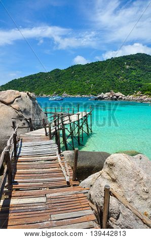 Wooden Bridge over crystal clear sea at Nangyuan Island in Thailand