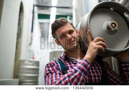 Portrait of happy brewer carrying keg at brewery factory