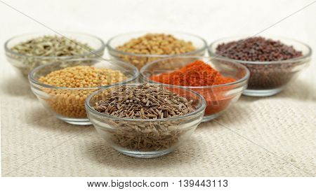 Different types of Indian spices in glass bowl, focus on cumin seeds on jute mat background. Front view.