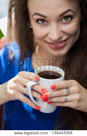 Girl Looking In The Camera With A Cup Of Coffe In Hands