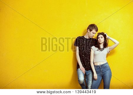 Couple In Fashion Posing On Yellow Wall