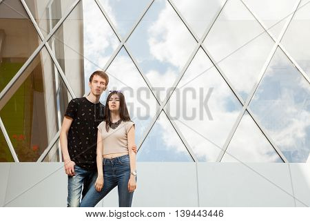 Beautiful Couple Posing Cool In Front Of Glased Office Building