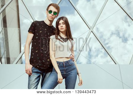 Gorgeous Young Couple Posing In Jeans In Front Of Office Glased Building