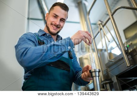 Happy brewer checking beer with hydrometer at brewery