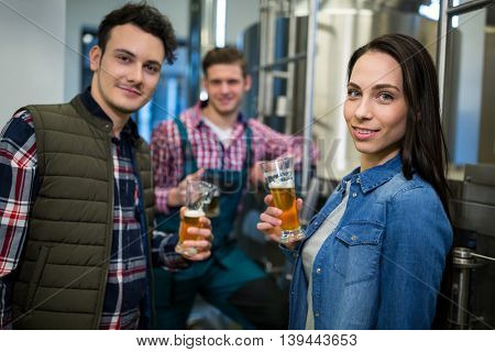 Portrait of brewers holding beer glasses at brewery factory