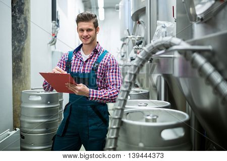 Portrait of maintenance worker writing on clipboard at brewery