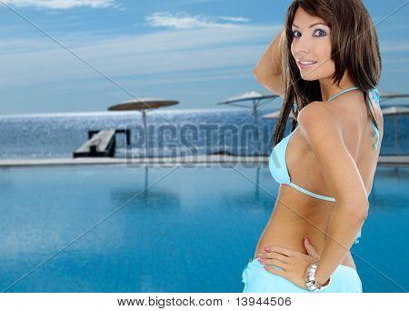 Beautiful young sexy woman standing in bikini next to swimming pool