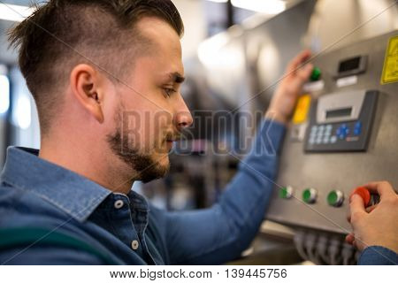 Close-up of maintenance worker operating control machine
