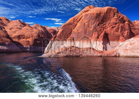 Red sandstone hills surround the lake. Foamy trace of a motor boat crosses the emerald waters. Lake Powell on the Colorado River