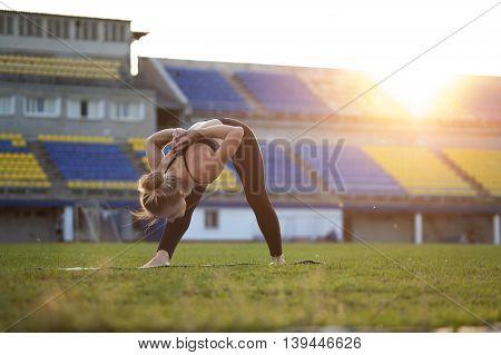 Fit blonde woman in sportswear doing yoga. Intense Side Stretch Pose.