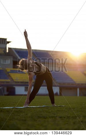 Fit blonde woman doing yoga exercise outdoors at sunset. Extended Triangle Pose
