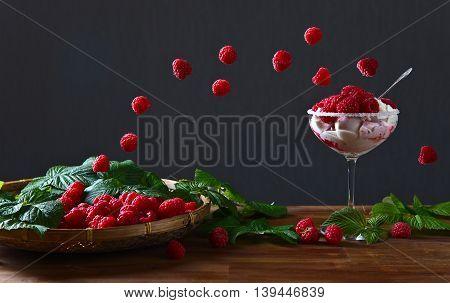 ice cream with ripe juicy raspberries on wooden table