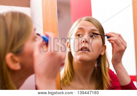 Woman doing make up with curved eyelash brushes in front of the mirror.