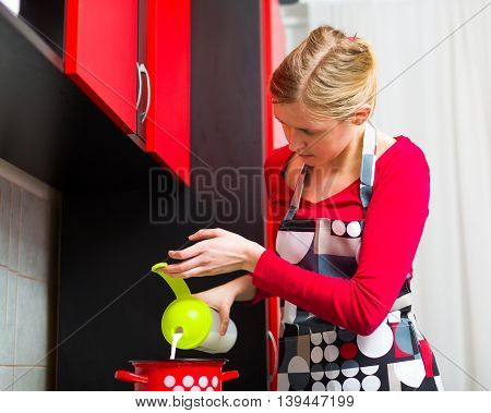 Busi blond woman in her reddish kitchen preparing domestic chocolate wearing colorful apron.