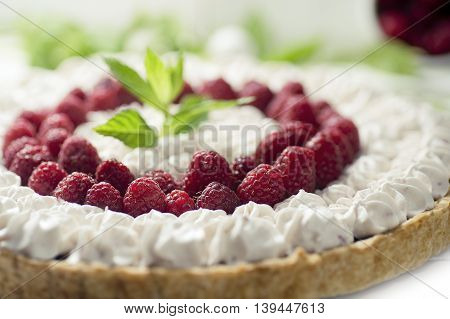 a macro / close-up of a red raspberry and whipped cream cake / pie decorated by a mint leaf
