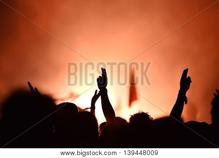 Audience With Hands Raised At A Music Festival And Lights Streaming