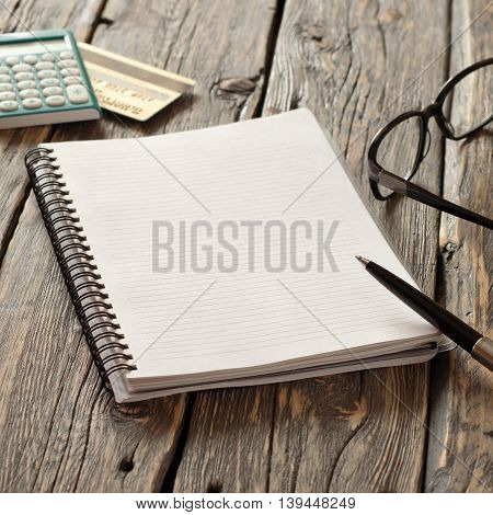 Open notebook with pen spectacles calculator and credit card Gold on the rough wooden table
