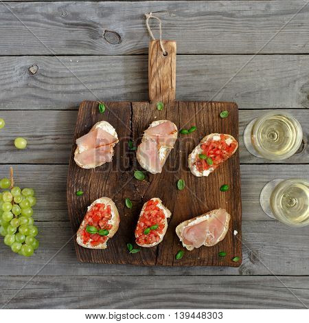 Sandwich with tomatoes goat cheese and ham on a wooden table. Wine with appetizers for wine