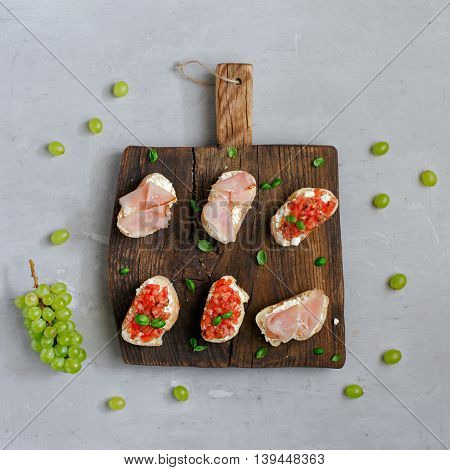 Sandwich with tomatoes goat cheese and ham on light surface top view. Appetizer for wine