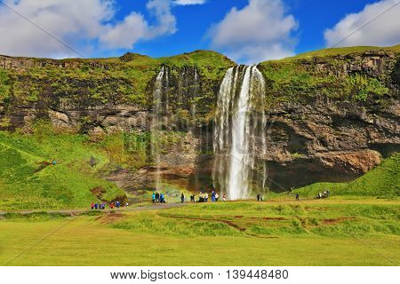 Typical landscape for the summer in Iceland. At the foot of the waterfall Seljalandsfoss crowds of tourists