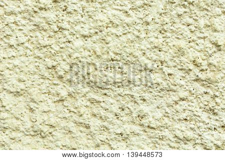 Plastered concrete surface with an uneven rough texture painted in a light green color