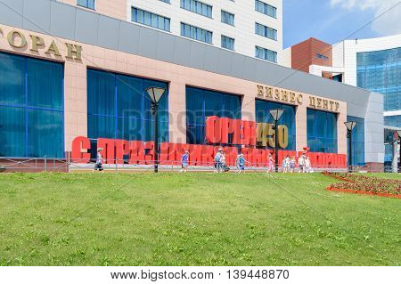 Orel, Russia - June 23, 2016: Group of children walk past solid 3D label