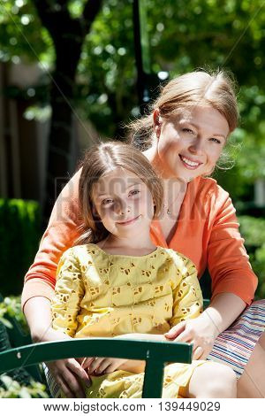 portrait of happy mother with daughter having good time in summer environment
