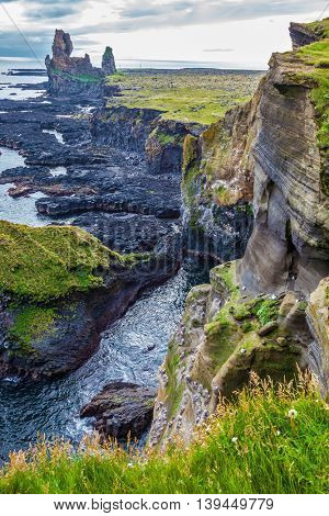 Magnificent Iceland. Northern sea coast. Picturesque ancient Skerries in cloudy summer day