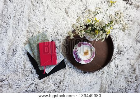 cup of coffee in bed with a cozy bedding and books