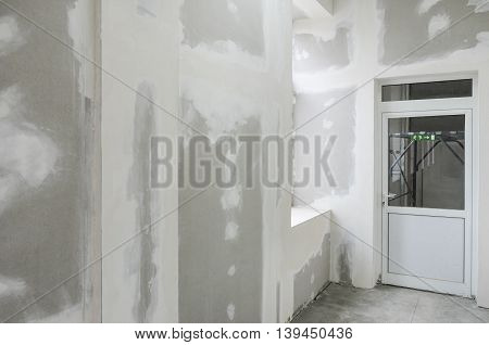 unfinished walls with gypsum and white door