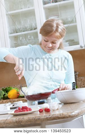 portrait of nice young woman cooking pancakes in kitchen environment
