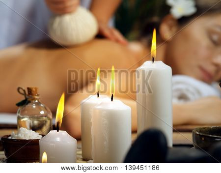 portrait of young beautiful woman  relaxing in spa environment. focused on candle.