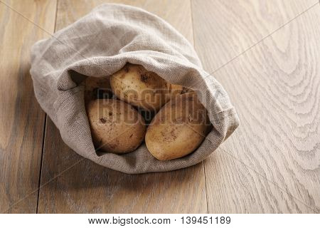 sack full of organic potatoes on oak wooden table with copy space, shallow focus