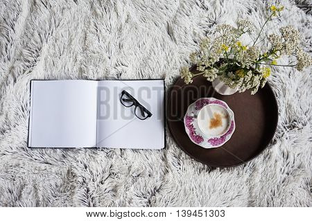 Cup of coffee in bed with a cozy bedding with a notebook