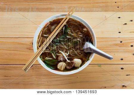 Rice noodle soup Cut White with Bean Sprout and Pork meatballs in a cup on a wooden background.