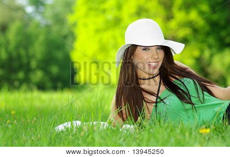 Beautiful woman sitting in the grass