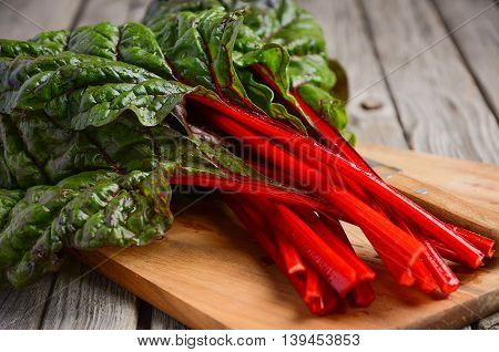 Fresh red chard leaves on wooden background, selective focus, copy space